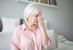 Старшая дама при мигрень касаясь ее лбу Стоковые Изображения RF