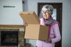 Старшая дама раскрывая коробку доставки стоковое фото