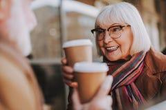 Старшая дама с горячим временем траты напитка с супругом в на открытом воздухе кафе стоковое фото