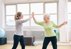 Старшая женщина давая максимум 5 к ее тренеру на спортзале Стоковое фото RF