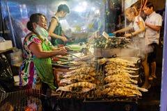 Старшая женщина варит рыб Стоковое фото RF