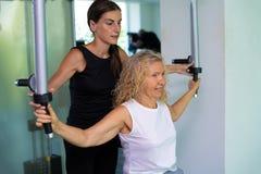Старшая женщина включена на имитаторе в спортзале с личным тренером дочь помогает маме в спортзале стоковые изображения rf