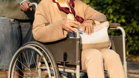 Старшая женщина в ее кресло-коляске стоковое фото rf