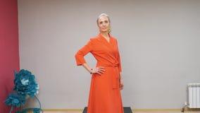 Старшая женщина в красном платье идя на подиум на модном параде Элегантная зрелая женщина показывая новую дизайнерскую одежду акции видеоматериалы
