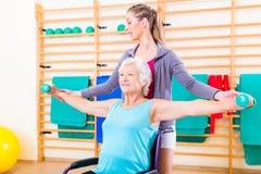 Старшая женщина в кресло-каталке делая физиотерапию Стоковые Фотографии RF