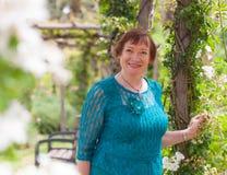 Старшая женщина в парке с розами Стоковая Фотография RF