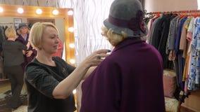 Старшая женщина в шляпе пробует пальто в магазине одежд сток-видео