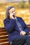 Старшая женщина говоря на smartphone outdoors Стоковое Изображение RF