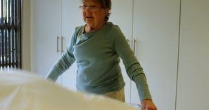 Старшая женщина делая кровать в спальне 4k видеоматериал