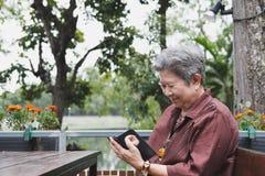 Старшая женщина держа мобильный телефон в саде пожилое женское texti Стоковые Изображения