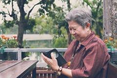 Старшая женщина держа мобильный телефон в саде пожилое женское texti Стоковая Фотография