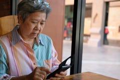 Старшая женщина держа мобильный телефон в саде пожилое женское texti Стоковое Фото