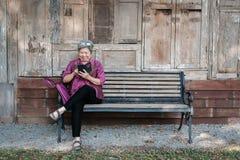 Старшая женщина держа мобильный телефон в саде пожилое женское texti Стоковое Изображение