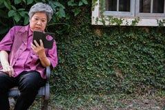 Старшая женщина держа мобильный телефон в саде пожилое женское texti Стоковые Фотографии RF