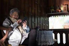 Старшая женщина держа мобильный телефон на террасе пожилой женский текст Стоковая Фотография