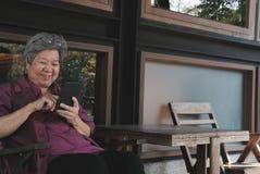 Старшая женщина держа мобильный телефон на террасе пожилой женский текст Стоковое Изображение