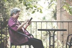 Старшая женщина держа мобильный телефон на террасе пожилой женский текст Стоковые Фото