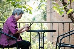 Старшая женщина держа мобильный телефон на террасе пожилой женский текст Стоковая Фотография RF