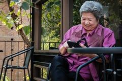 Старшая женщина держа мобильный телефон на террасе пожилой женский текст Стоковые Фотографии RF