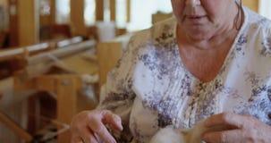 Старшая женщина держа шерстяную пряжу в руке 4k видеоматериал