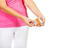 Старшая женщина держа пакет немногих таблеток стоковое изображение
