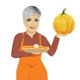 Старшая женщина держа свеже испеченный домодельный пирог тыквы иллюстрация вектора
