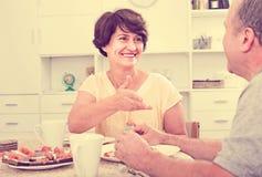 Старшая женщина есть с человеком дома стоковое фото rf