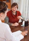 Старшая женщина жалуясь к доктору около чувствует Стоковое фото RF