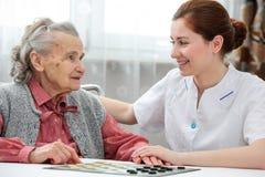 Старшая женщина играя контролеров Стоковое фото RF