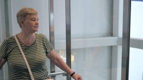 Старшая женщина идя вниз в стеклянный лифт видеоматериал