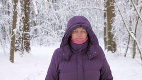 Старшая женщина идя вперед, и усмехаясь в лесе зимы сток-видео