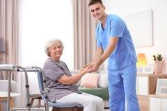 Старшая женщина идя с помощью молодого попечителя Стоковое фото RF
