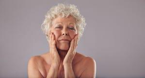 Старшая женщина изнеживая ее сторону стоковое фото