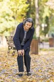 Старшая женщина имея боль колена идя в парке Стоковые Фото