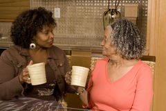 Старшая женщина имея кофе с ее дочерью Стоковые Изображения