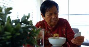 Старшая женщина используя мобильный телефон пока имеющ еду сток-видео