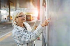 Старшая женщина используя таблетку стоковая фотография rf