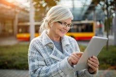 Старшая женщина используя таблетку стоковые изображения