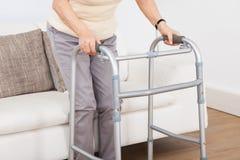 Старшая женщина используя идя рамку Стоковое Изображение