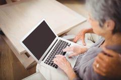 Старшая женщина используя компьтер-книжку в живущей комнате Стоковые Фото