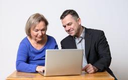 Старшая женщина используя компьютер около человека в костюме Стоковые Изображения RF