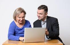Старшая женщина используя компьютер около человека в костюме Стоковые Фотографии RF