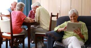 Старшая женщина используя цифровую таблетку видеоматериал