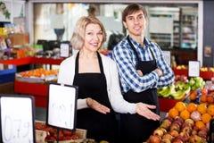 Старшая женщина и молодой человек предлагая сезонные плодоовощи стоковое фото rf