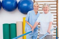Старшая женщина и терапевт усмехаясь на камере Стоковые Изображения RF