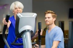 Старшая женщина и тренер усмехаясь на камере в студии фитнеса Стоковые Фотографии RF