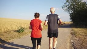 Старшая женщина и человек бежать или jogging на поле акции видеоматериалы