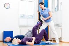 Старшая женщина и человек делая помогать вольные упражнения с physiot Стоковые Изображения