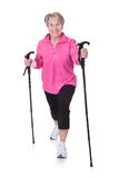 Старшая женщина идя с пешими поляками Стоковая Фотография