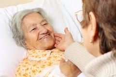 Старшая женщина лежа в кровати Стоковые Фото